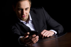 Zakenman die tekstberichten controleert op telefoon. Royalty-vrije Stock Afbeeldingen