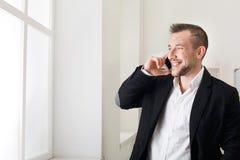Zakenman die telefonisch spreken, die zich dichtbij venster bevinden royalty-vrije stock foto's