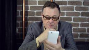 Zakenman die telefoon in een ruimte met een bakstenen muur met behulp van stock video