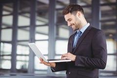 Zakenman die terwijl het gebruiken van laptop glimlachen Stock Afbeeldingen