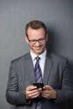 Zakenman die terwijl het gebruiken van smartphone glimlachen Stock Foto