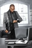 Zakenman die tijd controleert op kantoor stock afbeelding