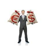 Zakenman die twee geldzakken houden royalty-vrije stock afbeeldingen