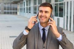 Zakenman die twee telefoons gelijktijdig met behulp van royalty-vrije stock afbeelding