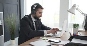 Zakenman die van muziek genieten en aan laptop werken stock footage