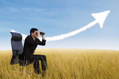Zakenman die verrekijkers met behulp van die het kweken van grafiekwolk bekijken Stock Foto's
