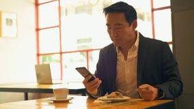 Zakenman die voedsel hebben terwijl het gebruiken van mobiele telefoon 4k stock video