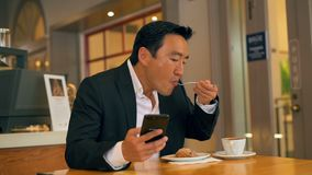 Zakenman die voedsel hebben terwijl het gebruiken van mobiele telefoon 4k stock footage