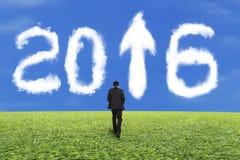 Zakenman die voor de witte wolk van 2016 en blauw hemelgras lopen Stock Foto's