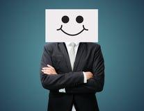 Zakenman die voorzijde van de het gezichtsholding van de Witboek de gelukkige glimlach bevinden zich Stock Afbeeldingen