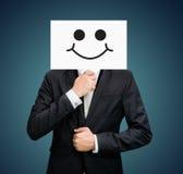 Zakenman die voorzijde van de het gezichtsholding van de Witboek de gelukkige glimlach bevinden zich Royalty-vrije Stock Foto