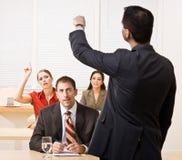 Zakenman die vragen in vergadering beantwoordt Stock Afbeeldingen