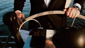 Zakenman die zich achter een stuurwiel op het schip bevinden Jonge zeeman die sailboard in zonnige dag drijven De mening van de c stock video