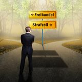 Zakenman die zich bij een kruispunt bevinden die tussen 'vrijhandel 'en 'tarief 'met verkeersteken in het Duits moeten beslissen royalty-vrije stock fotografie