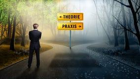 Zakenman die zich bij een kruispunt met de theorie van verkeersteken 'en 'praxis 'in het Duits bevinden stock afbeelding