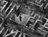 Zakenman die zich in centrum van 3D oud gevlekt concreet labyrint bevinden Royalty-vrije Stock Afbeelding