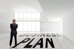 Zakenman die zich in een lege ruimte met het businessplan van woord bevinden royalty-vrije stock afbeelding