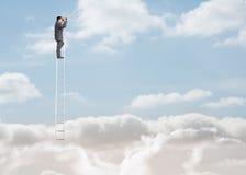 Zakenman die zich op een ladder over de wolken bevinden stock foto's