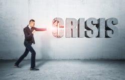 Zakenman die zich op grond bevinden die woord 'CRISIS' met vuist raken Royalty-vrije Stock Foto