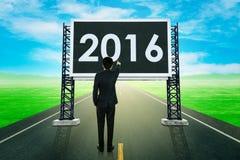 Zakenman die zich op weg bevinden en met groot teken van 201 richten Stock Foto