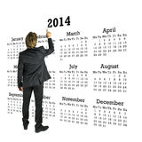 Zakenman die zich voor een kalender van 2014 bevinden Stock Afbeeldingen