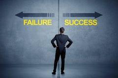 Zakenman die zich voor succes en mislukkingspijlconce bevinden Stock Afbeelding
