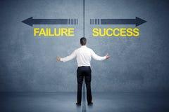 Zakenman die zich voor succes en mislukkingspijlconce bevinden Stock Afbeeldingen