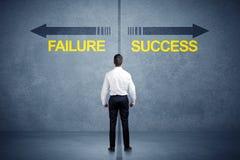 Zakenman die zich voor succes en mislukkingspijlconce bevinden Stock Fotografie