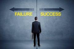Zakenman die zich voor succes en mislukkingspijlconcept bevinden Stock Afbeeldingen