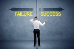 Zakenman die zich voor succes en mislukkingspijlconcept bevinden Stock Foto's