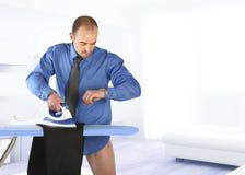 Zakenman die zijn broek strijkt Royalty-vrije Stock Afbeeldingen