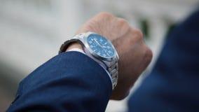 Zakenman die zijn horloge op zijn hand bekijken die op de tijd letten stock footage