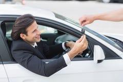 Zakenman die zijn nieuwe autosleutel krijgen Stock Afbeeldingen