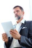 Zakenman die zijn tablet in het bureau gebruiken Royalty-vrije Stock Foto's