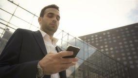 Zakenman die zijn telefoon bekijken en op iemand buiten het gebouw wachten stock footage