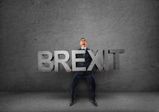 Zakenman die zware 3d & x27 houden; brexit& x27; woord in zijn handen Stock Afbeeldingen