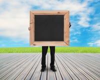 Zakenman die zwart leeg bord met natuurlijke hemelweide houden Stock Afbeelding