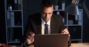 Zakenman door slecht nieuws op laptop laat in nachtbureau dat wordt gefrustreerd stock videobeelden