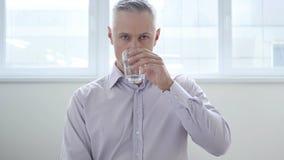Zakenman Drinking Water in Bureau stock foto