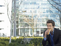 Zakenman Eating Sandwich In Front Of Office Building royalty-vrije stock fotografie