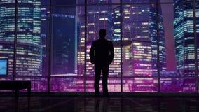 Zakenman in een bureau op een achtergrond van nachtwolkenkrabbers stock videobeelden