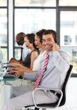 Zakenman in een call centre dat bij de camera glimlacht Stock Fotografie