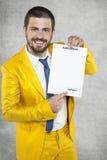 Zakenman in een kostuum die een gouden contract voor het werk houden stock foto