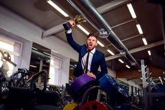 Zakenman in een kostuum met een kampioenskop in de gymnastiek stock afbeeldingen