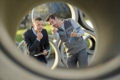 Zakenman en arbeider die door cementpijp kijken Royalty-vrije Stock Foto