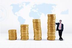 Zakenman en de gouden grafiek van de muntstukkengroei Stock Afbeeldingen