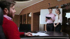 Zakenman en de vrouw die een presentatie en hun werkgever de doen luisteren aan hen stock videobeelden