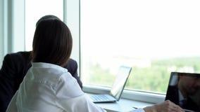 Zakenman en donkerbruine onderneemster het mooie spreken op het werk terwijl het zitten door het venster in het bureau stock videobeelden