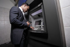 Zakenman en een ATMmachine Stock Afbeelding