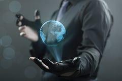 Zakenman en een hologram van de aarde Stock Foto's